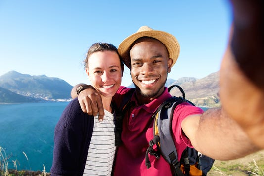 Smiling Young Couple On Vacation Taking Selfie