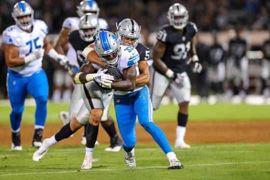 Detroit Lions running back Kerryon Johnson (33) gets tackled by Oakland Raiders linebacker Kyle Wilber (58) during the third quarter at Oakland Coliseum on Aug. 10, 2018, in Oakland, California.