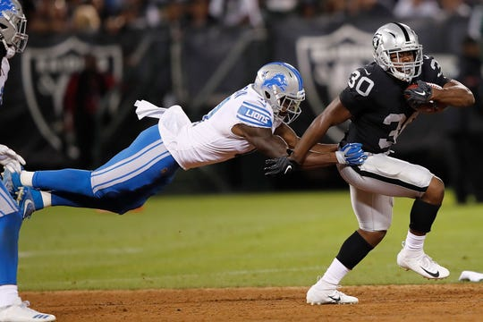 Oakland Raiders running back Jalen Richard (30) carries against Detroit Lions defensive back Rolan Milligan during the first half of an NFL preseason football game in Oakland, Calif., Friday, Aug. 10, 2018.