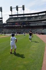Eric Rojas, 8 years old, plays catch with Detroit Tigers designated hitter Victor Martinez on Saturday, Aug. 11, 2018.