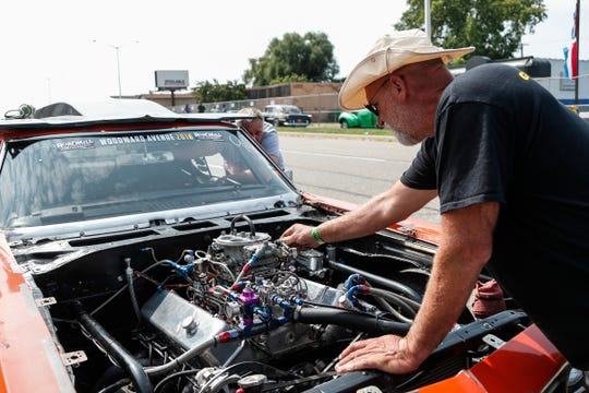 John Castelein, right, helps John Maher, center, solve problems on the 1969 Chevrolet Chevelle during Roadkill Nights Powered by Dodge in Pontiac, Saturday, August 11, 2018.