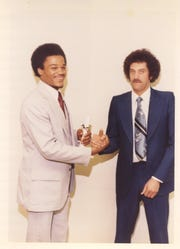 Saginaw star Milton Barnes shakes hands with coach Charlie Coles after graduation in 1975,