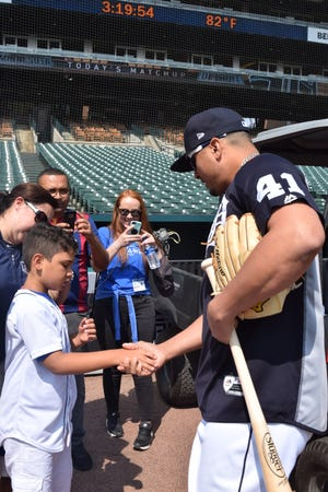 Eric Rojas, 8 years old, shakes hands with Detroit Tigers' Victor Martinez on Saturday, Aug. 11, 2018.