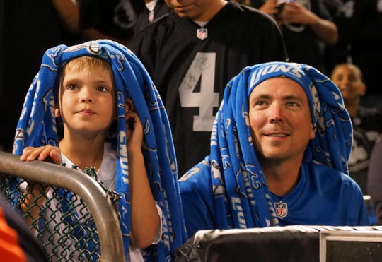 Two Detroit Lions fans with headgear made of fleece material look on during half time against the Oakland Raiders at Oakland Coliseum on Aug. 10, 2018.