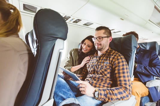Young People Traveling By Airplane Using Digital Tablet