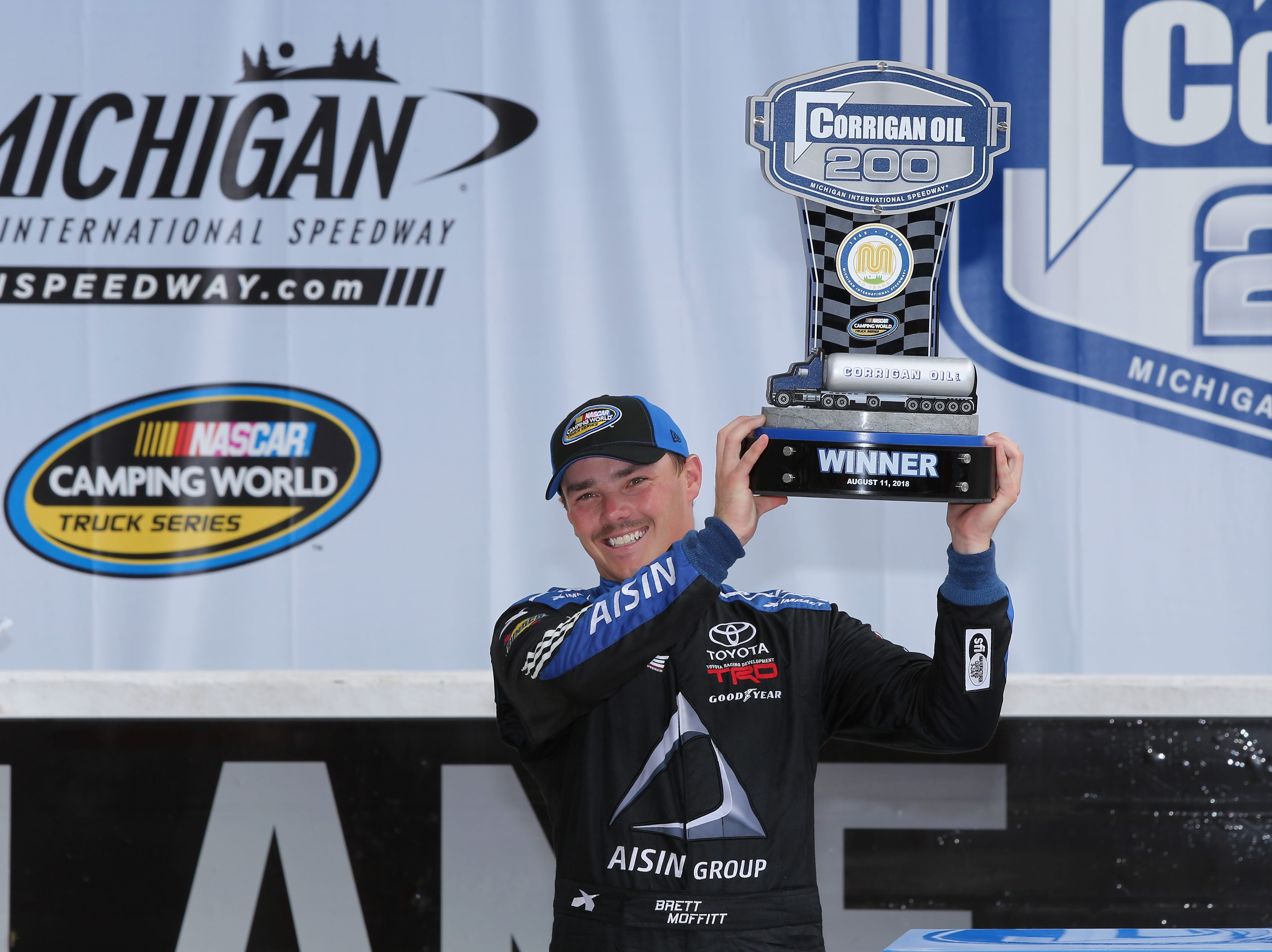 Brett Moffitt, driver of the No. 16 Hino Toyota, poses with the trophy in Victory Lane after winning the NASCAR Camping World Truck Series Corrigan Oil 200 at Michigan International Speedway on August 11, 2018 in Brooklyn.