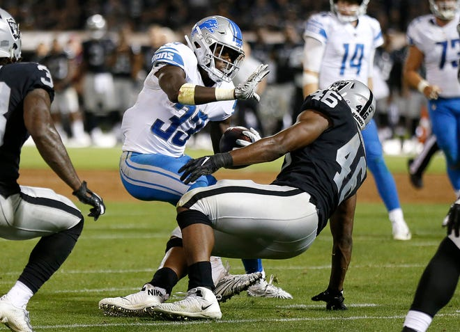 Detroit Lions running back Kerryon Johnson (33) carries as Oakland Raiders linebacker Jason Cabinda defends during the second half.