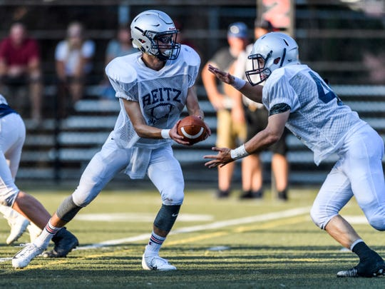 Reitz's Eli Wiethop (1) hands off to Adam Euler (44) during a preseason scrimmage against Mater Dei last Friday at the Bowl.