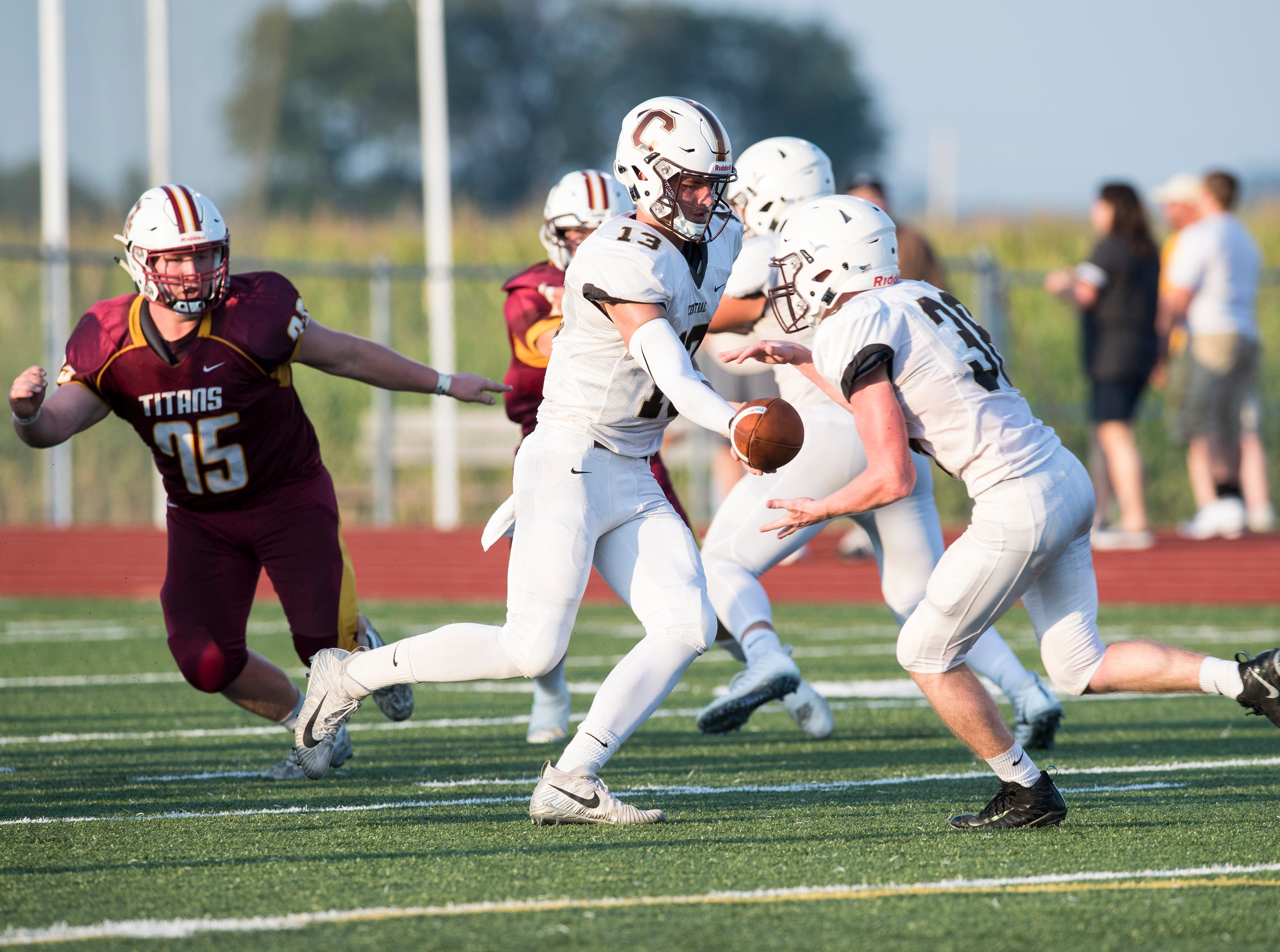 Central's Quarterback Brennon Harper (13) hands the ball off to teammate Brennan Schutte (38) during a scrimmage against Gibson Southern Friday, August 10, 2018.