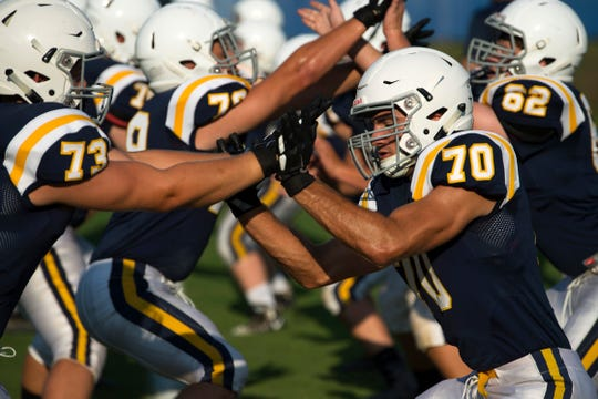Castle's Graham Tilly (73) and Seth Miles (70) run through warm-up drills before their scrimmage against Memorial at John Lidy Field in Paradise, Ind.