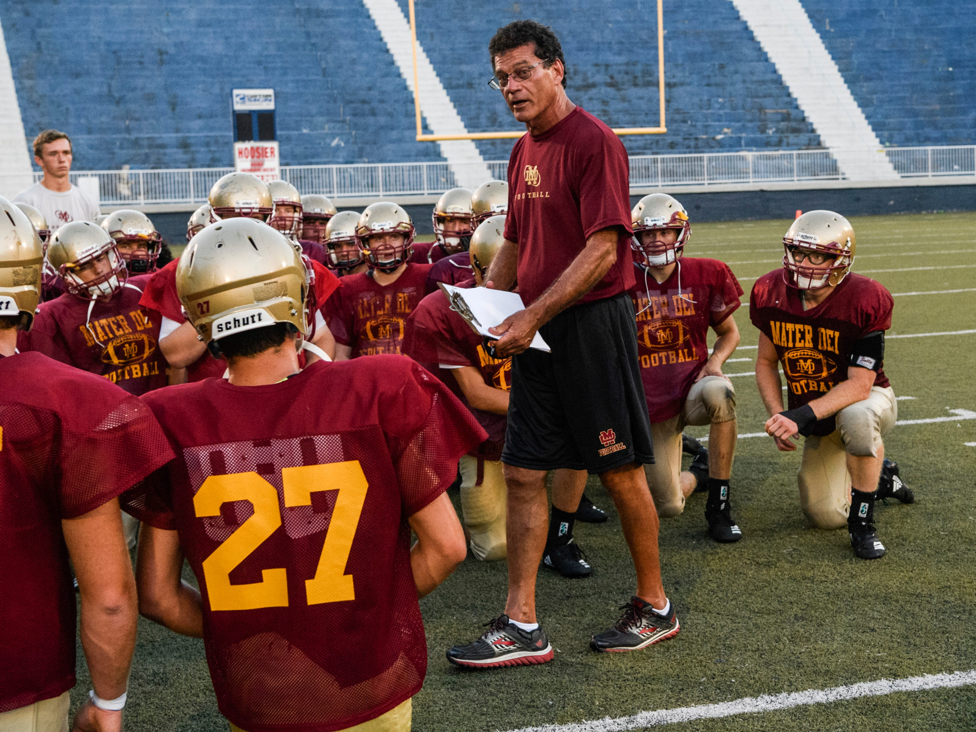 Mater Dei Head Coach Mike Goebel talks to his team after finishing a scrimmage against the Reitz Panthers at the Reitz Bowl in Evansville, Ind., Friday, Aug. 10, 2018. They will play Indian Creek in Trafalgar, Ind., next Saturday, August 18.