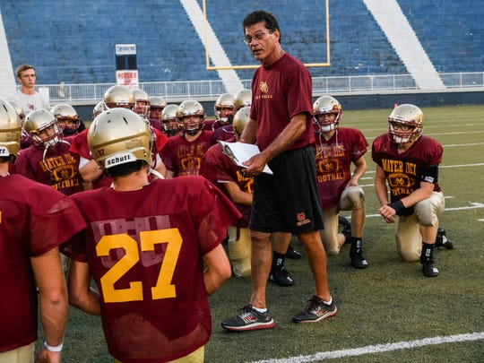 Mater Dei Head Coach Mike Goebel talks to his team after finishing a scrimmage against the Reitz Panthers at the Reitz Bowl in Evansville, Ind., Friday.