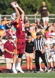 Gibson Southern's Dawson Witte (12) catches the pass over his head during a scrimmage against the Evansville Central Bears Friday, August 10, 2018.