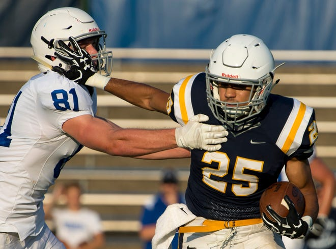 Castle's Noah Taylor, straight-arming Memorial's Branson Combs in a scrimmage, ran for a career-high 249 yards and scored four TDs in the Knights' romp over Terre Haute South.