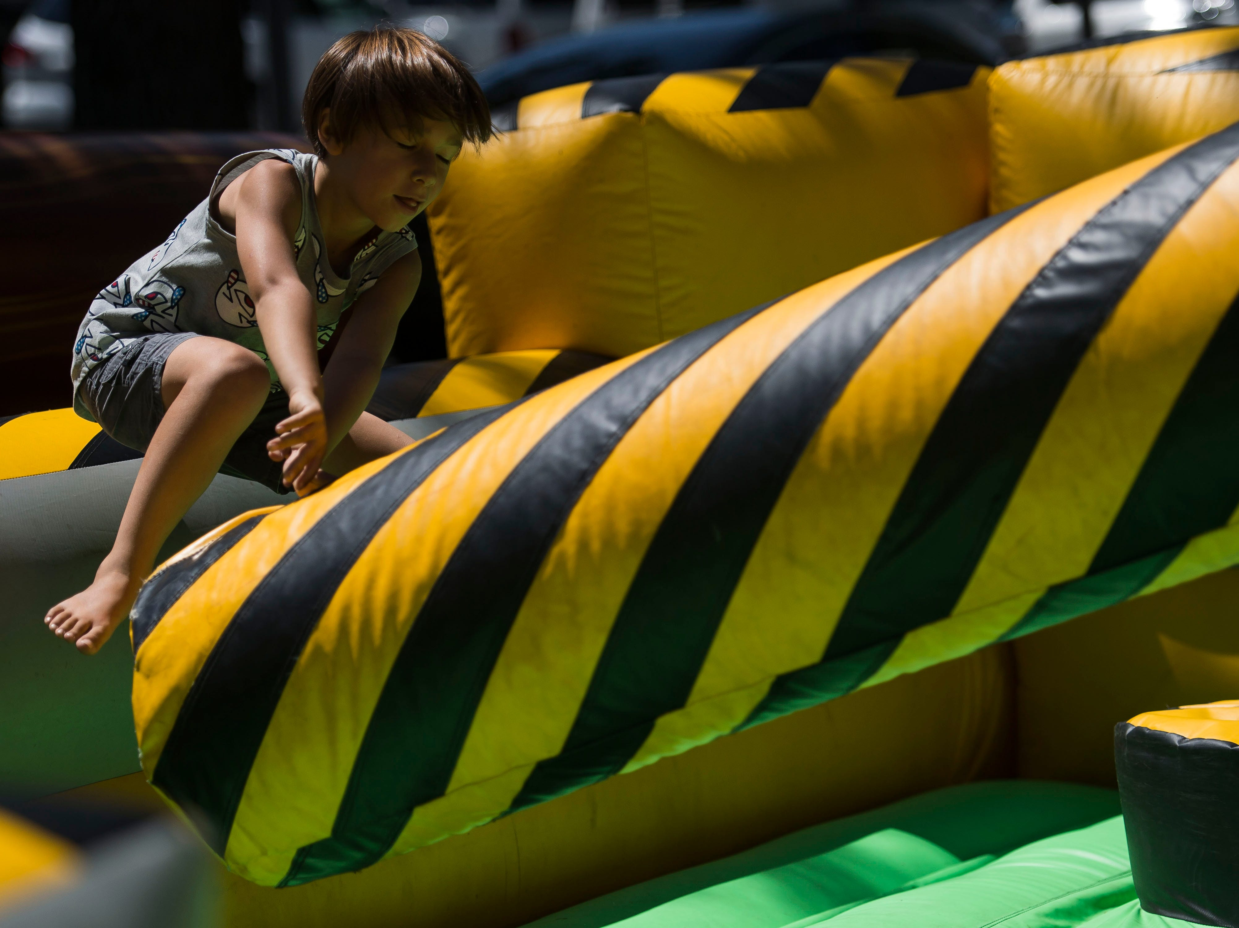 Mason O'Shea-Thompson leaps over an inflatable arm during the second day of Bohemian Nights at NewWestFest on Saturday, Aug. 11, 2018, in Old Town Fort Collins, Colo.