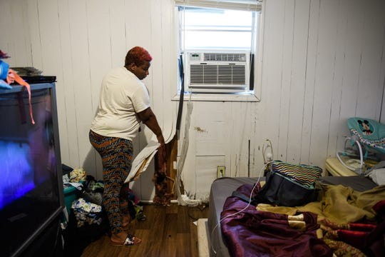 Teonna Williams lifts up a section of her bedroom wall that is water damaged on Saturday, Aug. 11, 2018. The wall has a hole where she said rats dug through into her apartment. Williams says she is staying in her apartment for the time being because she doesn't have another place to stay, despite the place being condemned by the Greenville County Code Enforcement.