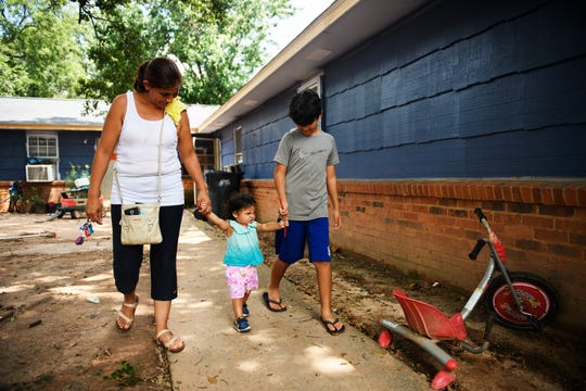 Glendy Ramirez and her children Christopher, 10, and Michelle, 1, leave their apartment to sell laundry detergent on the side of the road to pay for a hotel room on Saturday, Aug. 11, 2018.
