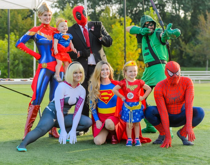 2 year old Harper Hunter (front) and sister, McKayla (back) poses for a picture with volunteers from SC Upstate Heros during the 4th annual Superhero 5K to benefit The Salvation Army Boys & Girls Club is held on Saturday, August 11, 2018 at the Kroc Center in Downtown Greenville.