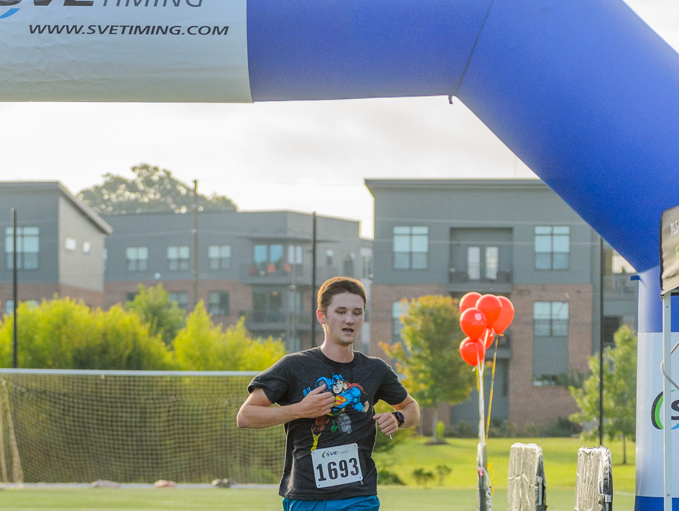 Grayson Martin crosses the finish line to come in 1st place during the 4th annual Superhero 5K to benefit The Salvation Army Boys & Girls Club is held on Saturday, August 11, 2018 at the Kroc Center in Downtown Greenville.