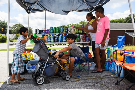 Christopher Soria-Ramirez, 10, and his brother Kevin, 4, play with their sister Michelle, 1, as their mother Glendy and Junior Marcial sell laundry detergent on Washington Street to pay for a hotel room for the night on Saturday, Aug. 11, 2018.