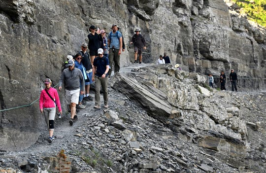"This photo taken July 27, 2018, shows a line of hikers walk the beginning of the Highline Trail, which starts at the Logan Pass Visitor's Center on the Continental Divide in Glacier National Park. ""You can still find solitude in the park,"" says frequent park visitor Matthew Kreuter, ""but you gotta get eight to ten miles in.""  (Kurt Wilson /The Missoulian via AP)"