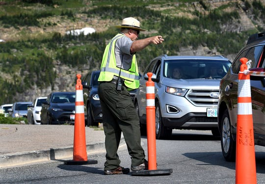 This photo taken July 27, 2018, shows Emlon Stanton, a visitor service assistant in Montana's Glacier National Park, directing traffic by the closed entrance to the full parking lot at Logan Pass . Parking lot attendants will close the popular lot for 20 to 30 minutes at a time to let traffic already circling the lot thin out before opening it up again. (Kurt Wilson /The Missoulian via AP)