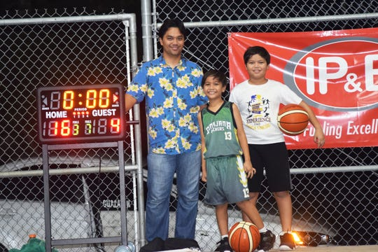 Sinajana Youth Basketball League founder Vincent Duenas and his sons Tomas, 9, and Vincent Jr., 11, after a game Aug. 10 at the Sinajana Gym. Both sons know how to fill out a scoresheet and run the game clock, Vincent Duenas said.