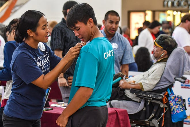 "Jennifer Camacho, left, wife of attorney general candidate Leevin Camacho, places a election button on Camden Camacho as her husband chats with a constituent during an ""One on One with the Candidates"" event in the center court of the Micronesia Mall in Dededo on Saturday, Aug. 11, 2018."