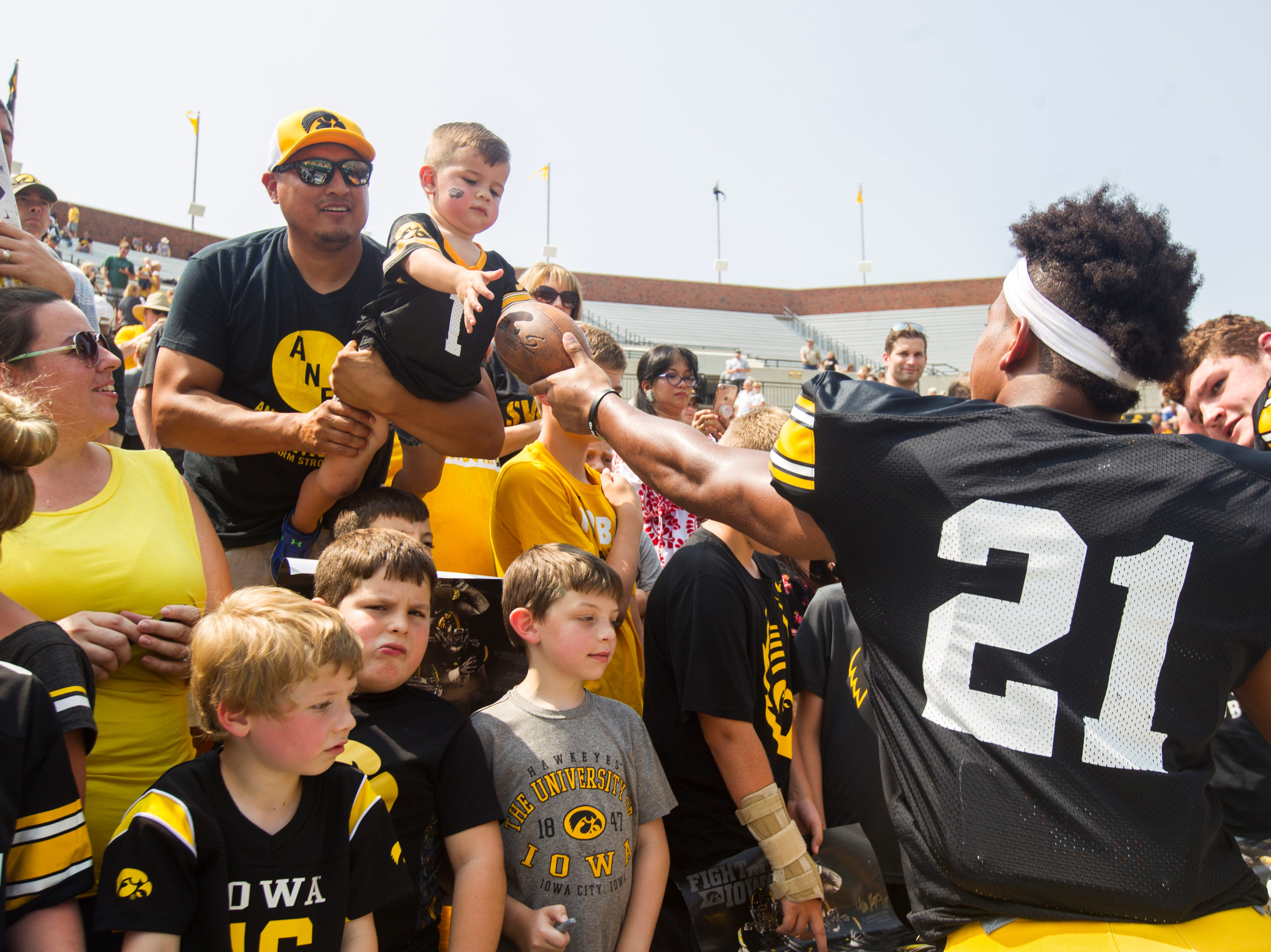 Iowa running back Ivory Kelly-Martin hands a signed football to a young fan during a Kids Day practice on Saturday, Aug. 11, 2018, at Kinnick Stadium in Iowa City.