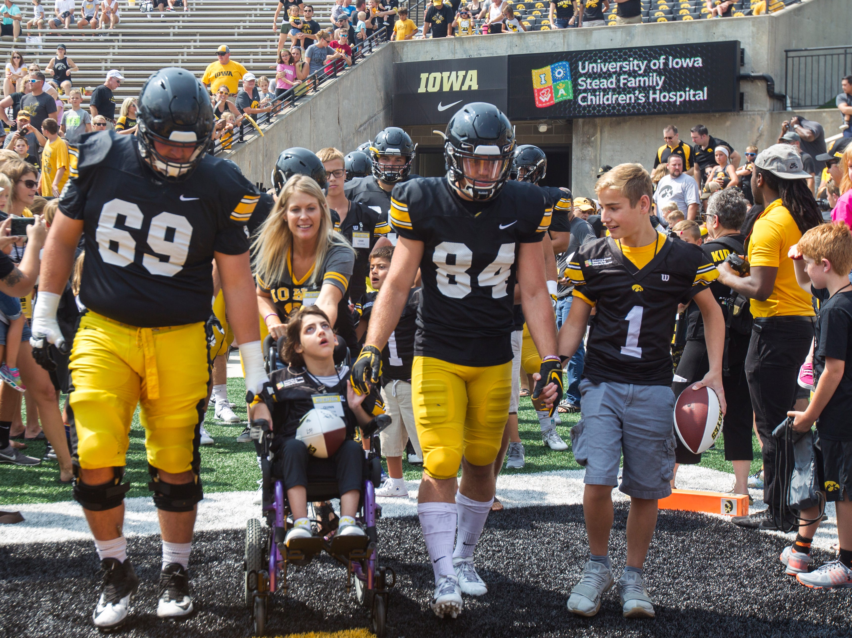 Iowa offensive lineman Keegan Render and wide receiver Nick Easley walk out of the tunnel with Kid Captains during a Kids Day practice on Saturday, Aug. 11, 2018, at Kinnick Stadium in Iowa City.