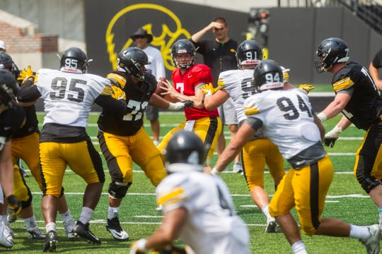 Iowa quarterback Spencer Petras looks for a receiver while defensive linemen Cedrick Lattimore and Brady Reiff apply pressure during a Kids Day practice on Saturday, Aug. 11, 2018, at Kinnick Stadium in Iowa City.