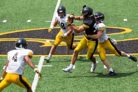 Iowa tight end T.J. Hockenson catches a pass while being covered by defensive back John Milani and during a Kids Day practice on Saturday, Aug. 11, 2018, at Kinnick Stadium in Iowa City.