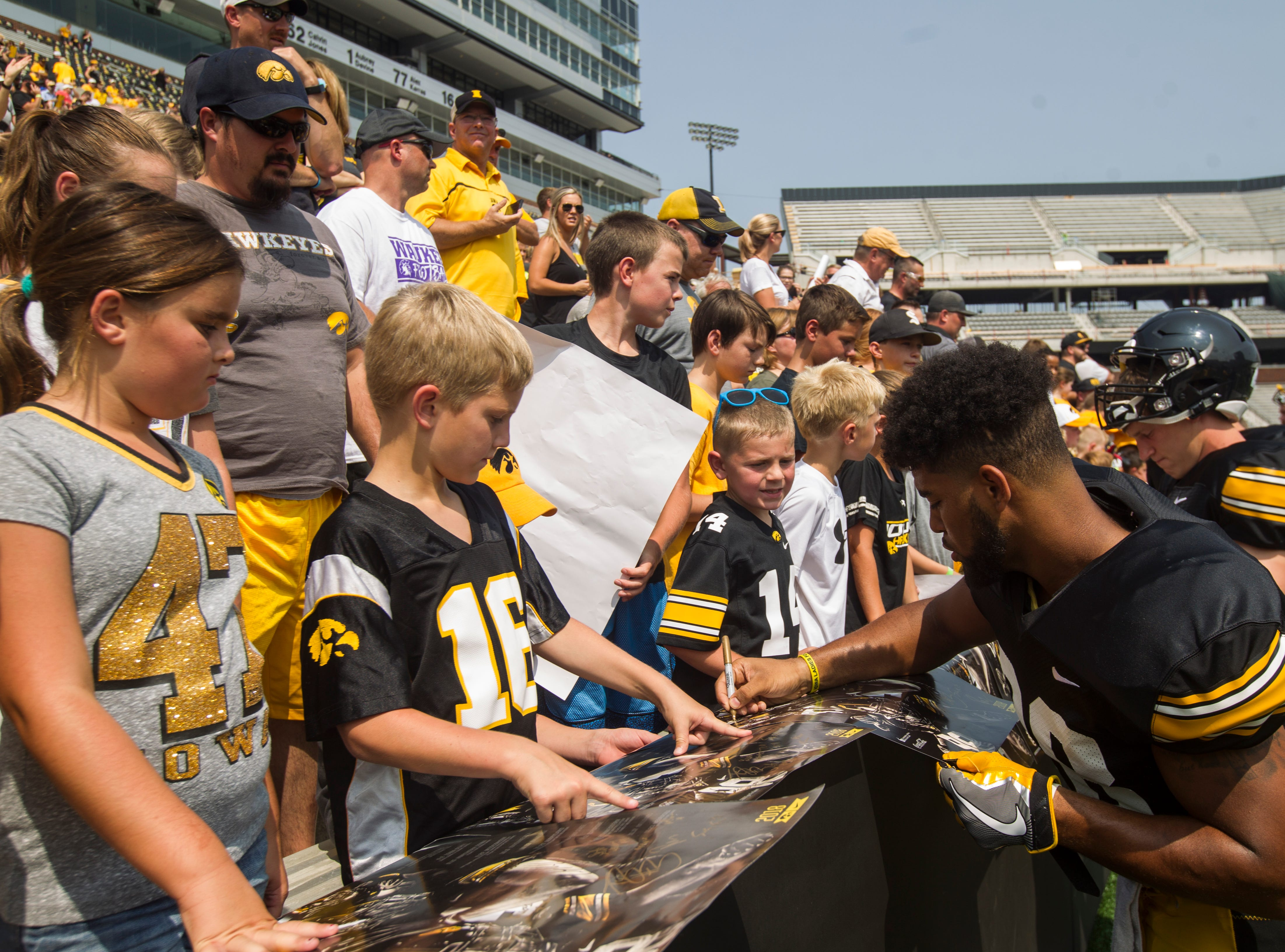 Iowa running back Toren Young signs autographs for fans during a Kids Day practice on Saturday, Aug. 11, 2018, at Kinnick Stadium in Iowa City.