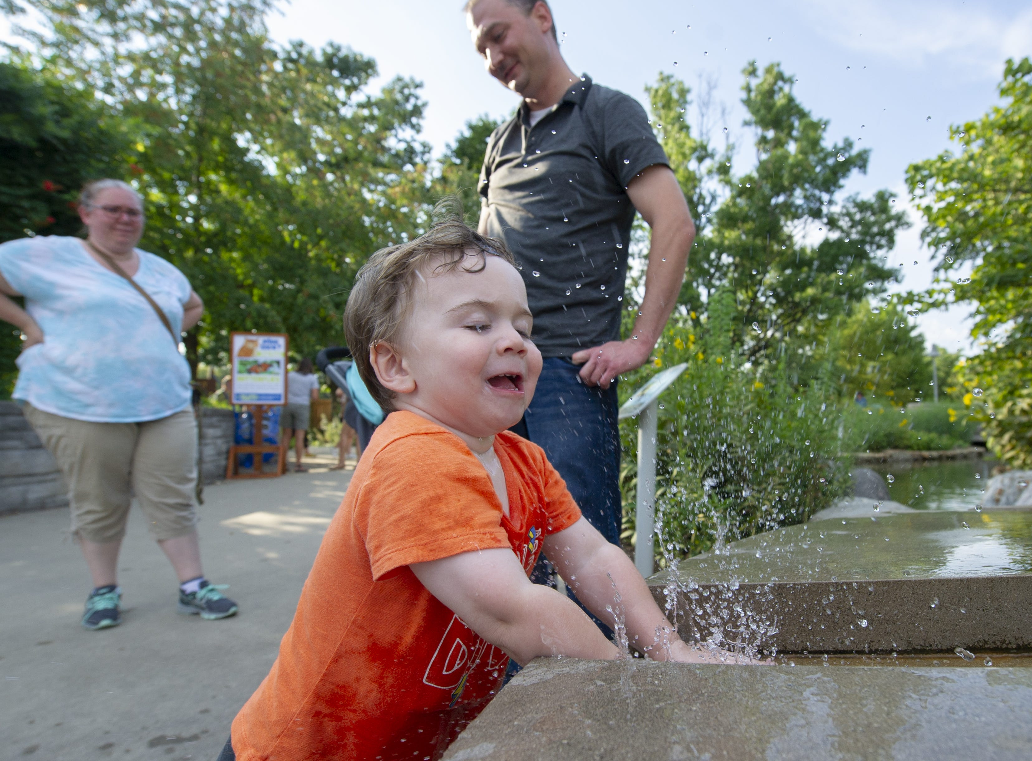Connor Dermody, 2, of McCordsville, splashes in the water flowing from a fountain in the Department of Natural Resources area at the Indiana State Fair, Friday, Aug. 10, 2018. His parents, Elisabeth and Mark let him cool off with his play.