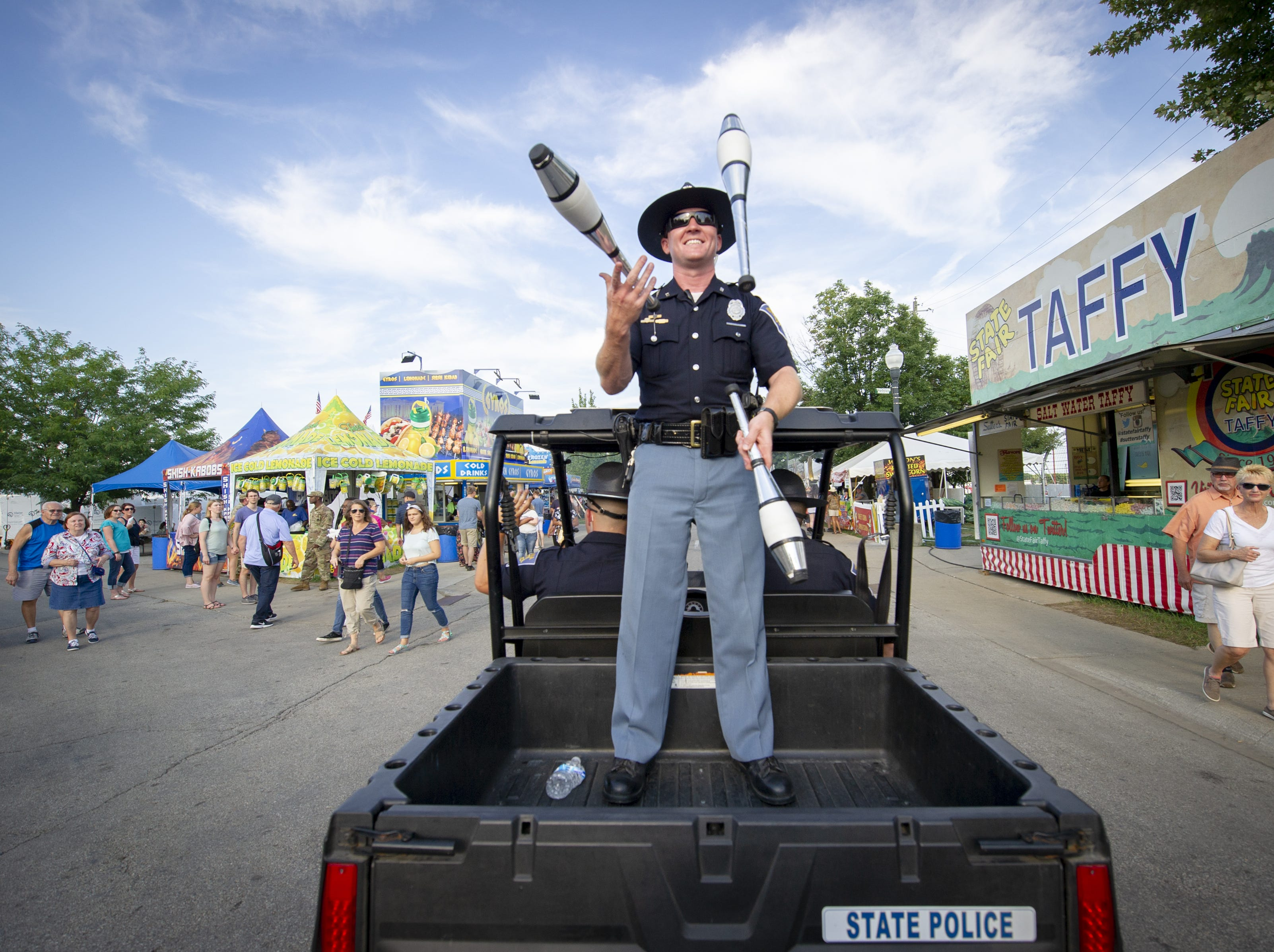 Indiana State Trooper Jon Cole juggles from the back of a vehicle as they lead an evening parade around the grounds at the Indiana State Fair, Friday, Aug. 10, 2018.