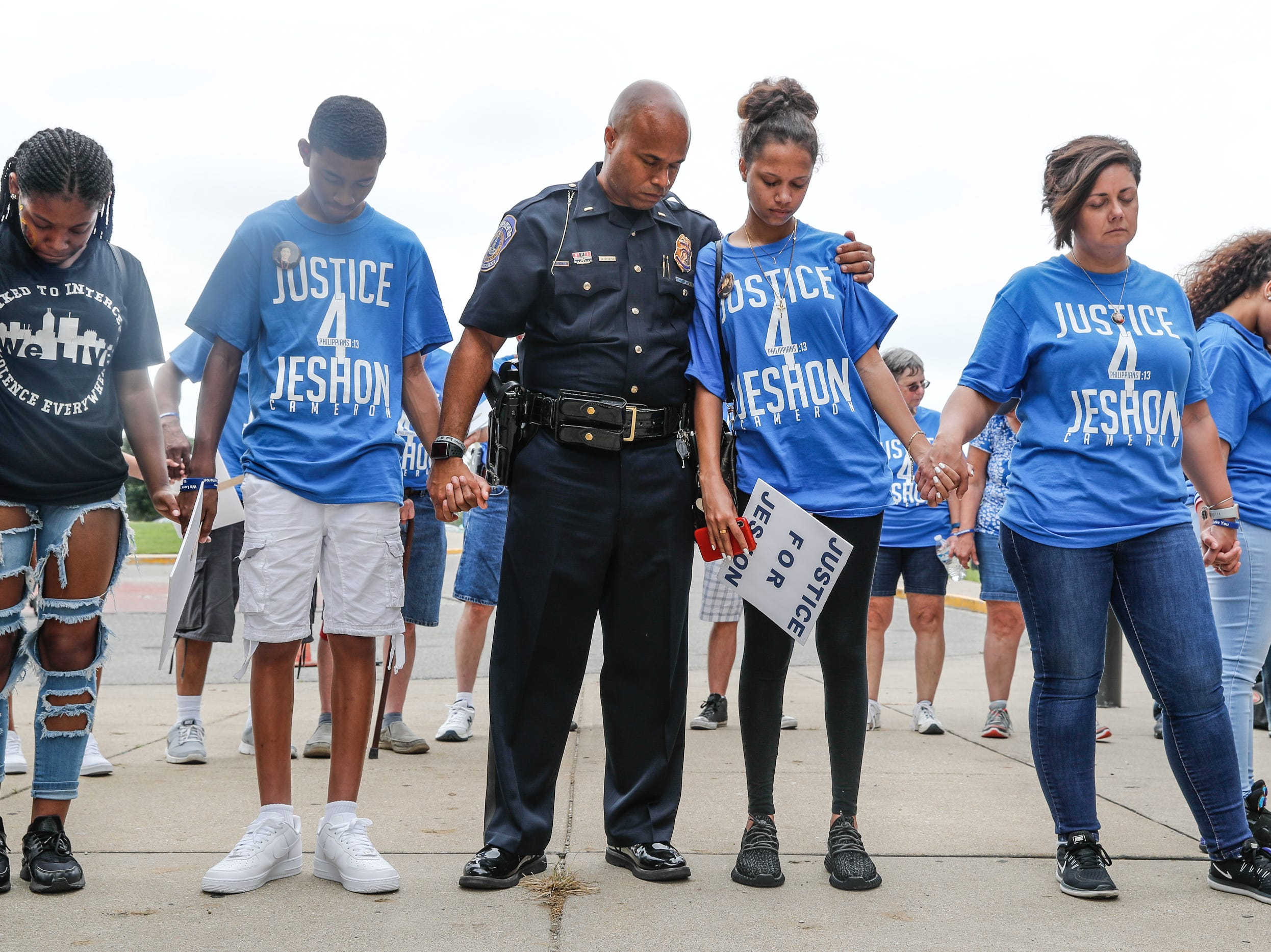 IMPD Public Information Officer, Kendale Adams comforts Divina Leal, who lost her boyfriend JeShon Cameron and her mother Josie Jones to gun violence, during the 'We Live' second annual Peace Walk and community day to end youth violence at Washington Park on Saturday, Aug. 11, 2018. 'We Live,' which stands for 'Linked To Intercept Violence' was started by students from Warren Central High School in Indianapolis.