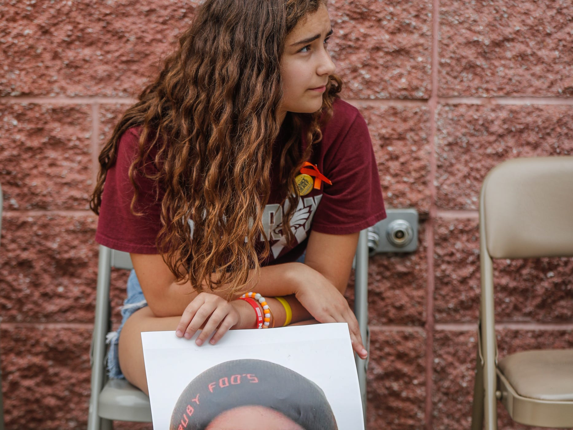 Isabella Fallahi holds a photo of friend Joaquin Olive, a victim of the Marjory Stoneman Douglas High School mass shooting, during the second annual Peace Walk and Community Day to end youth violence at Washington Park on Saturday, Aug. 11, 2018. 'We Live,' which stands for 'Linked To Intercept Violence' was started by students from Warren Central High School in Indianapolis.