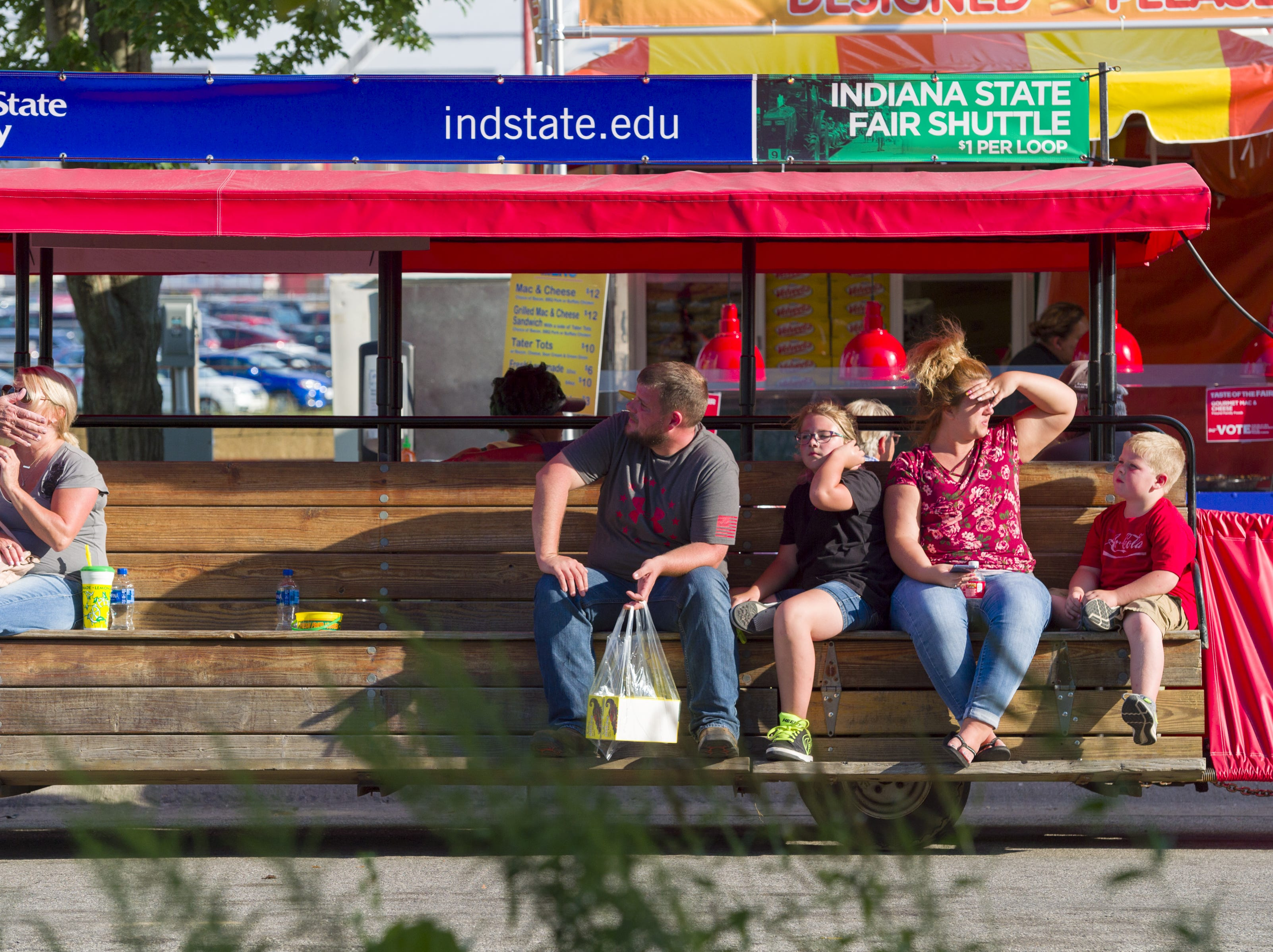 Fair goers ride the shuttle around the grounds at the Indiana State Fair, Friday, Aug. 10, 2018.