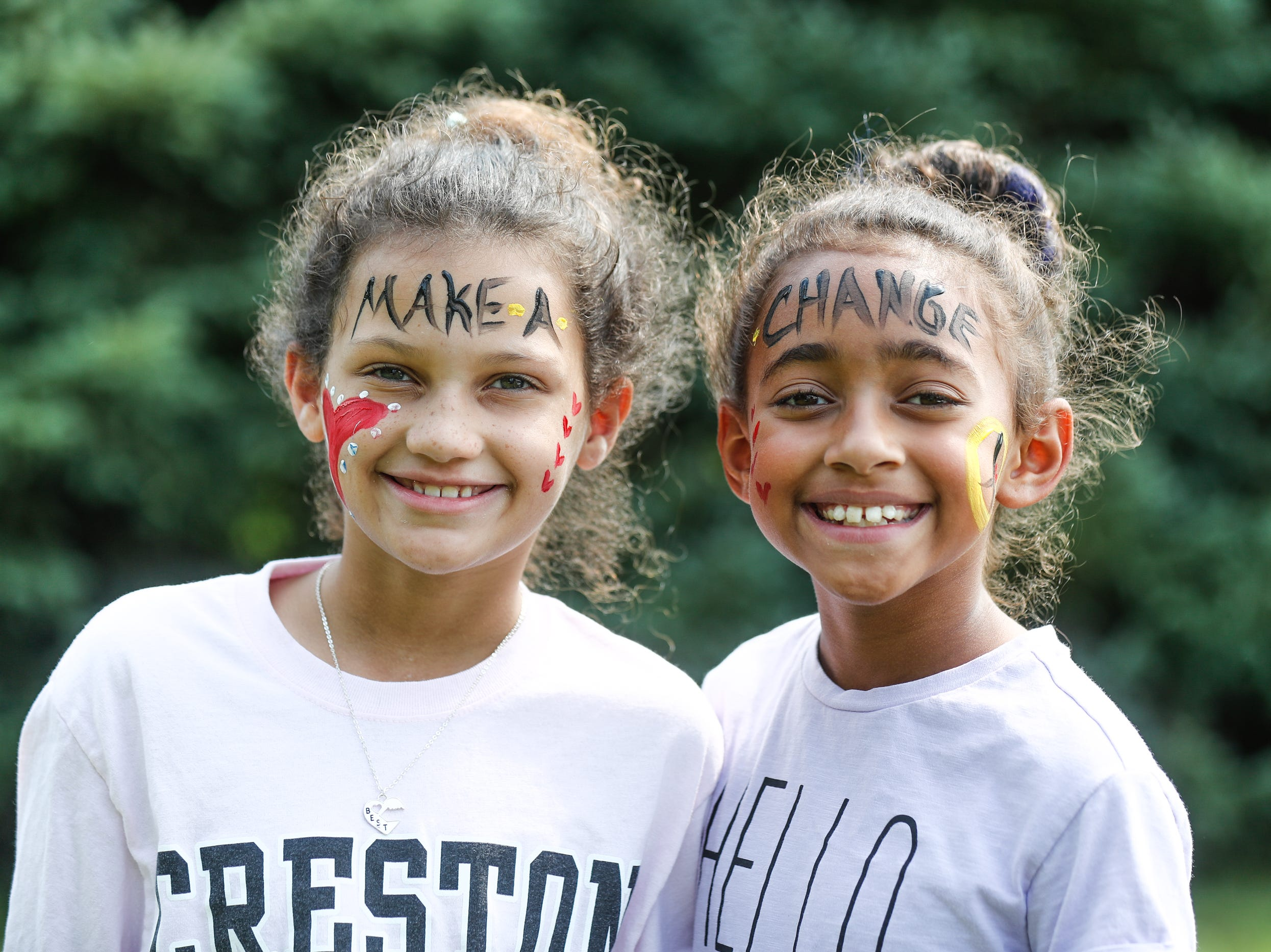Best friends Malia Hillsman left, and Natalie Hilliard have their faces painted during the 'We Live' second annual Peace Walk and Community Day to end youth violence at Washington Park on Saturday, Aug. 11, 2018. ''We Live,' which stands for 'Linked To Intercept Violence' was started by students from Warren Central High School in Indianapolis.