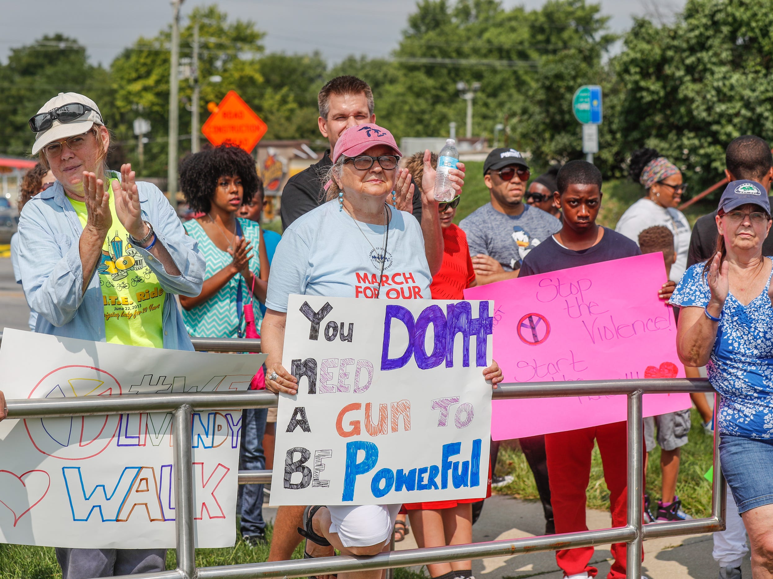 Members and supporters of 'We Live' stop for a prayer at the Marion County Juvenile Center during their second annual Peace Walk and community day to end youth violence at Washington Park on Saturday, Aug. 11, 2018. 'We Live,' which stands for 'Linked To Intercept Violence' was started by students from Warren Central High School in Indianapolis.