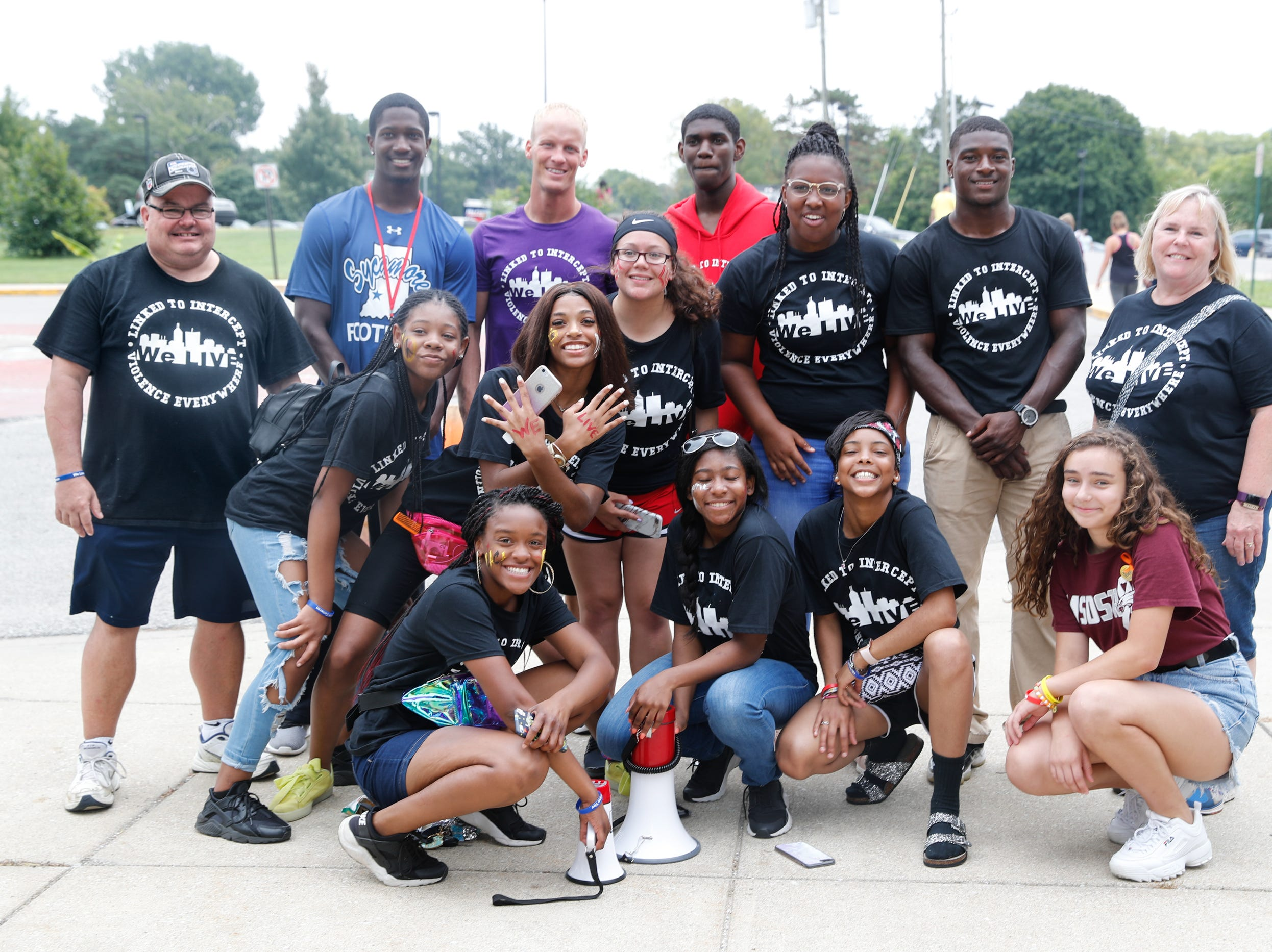 Members of 'We Live' pose for a group photo during their second annual Peace Walk and Community Day to end youth violence at Washington Park on Saturday, Aug. 11, 2018. 'We Live,' which stands for 'Linked To Intercept Violence' was started by students from Warren Central High School in Indianapolis.