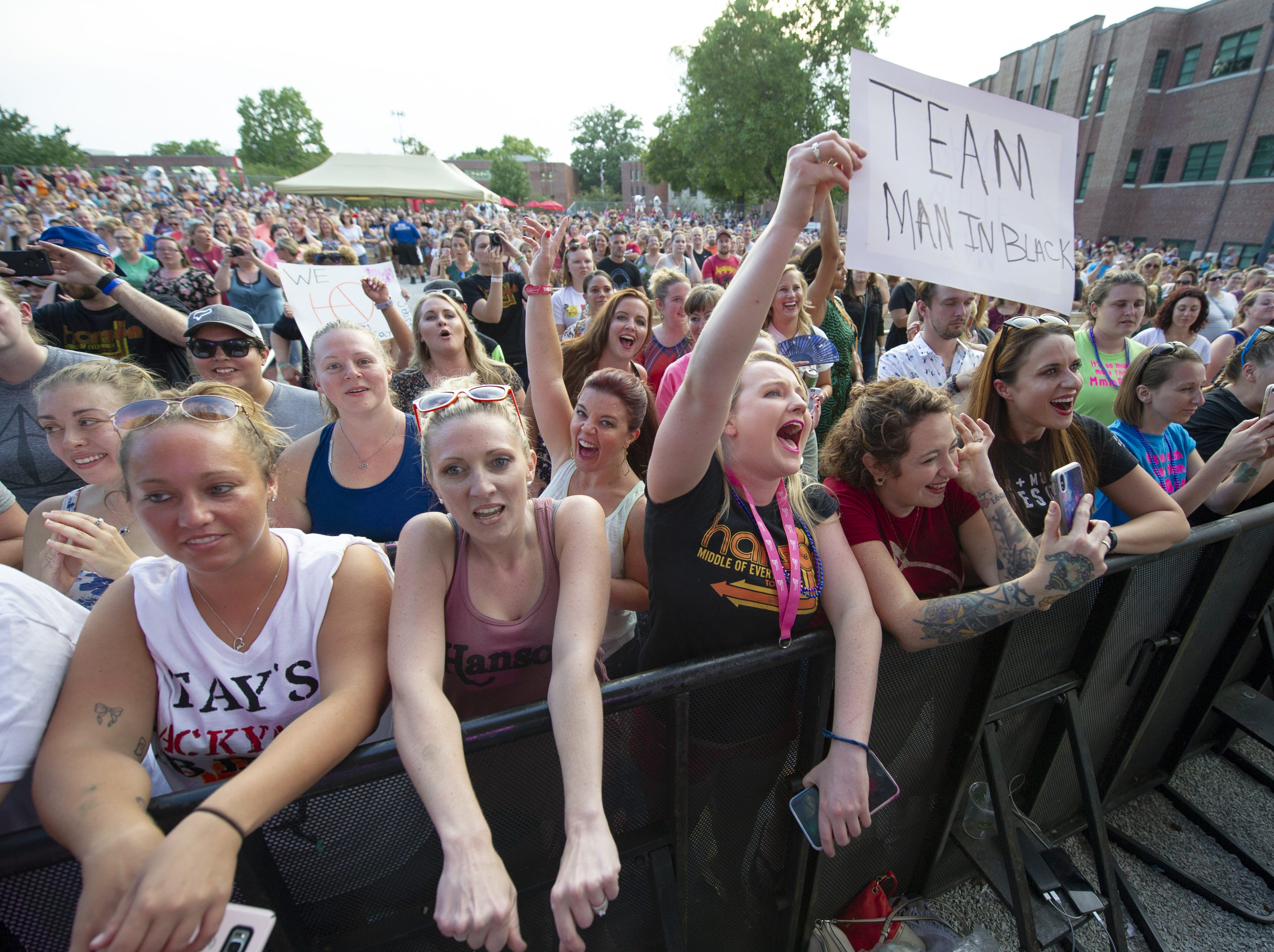 """Fans cheer as Hanson performs on stage. Hanson, a trio of siblings known for the No. 1 hit in 1997 titled """"MMMBop"""" performed at the Indiana State Fair, Friday, Aug. 10, 2018, on the Chevrolet Free Stage."""