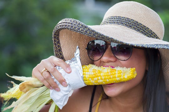Sarah Delima, of Indianapolis, digs in to an ear of corn at the Indiana State Fair, Friday, Aug. 10, 2018.