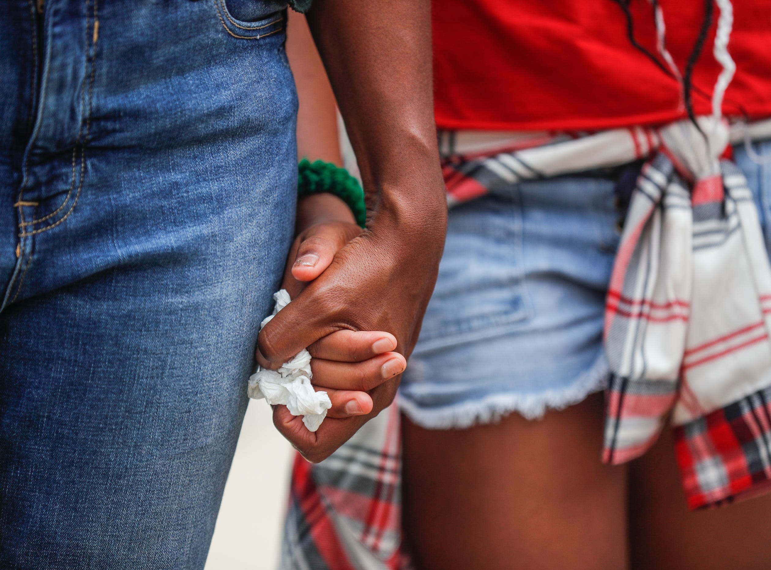 Supporters of 'We Live'' hold hands in prayer during the second annual Peace Walk and Community Day to end youth violence at Washington Park on Saturday, Aug. 11, 2018. 'We Live,' which stands for 'Linked To Intercept Violence' was started by students from Warren Central High School in Indianapolis.