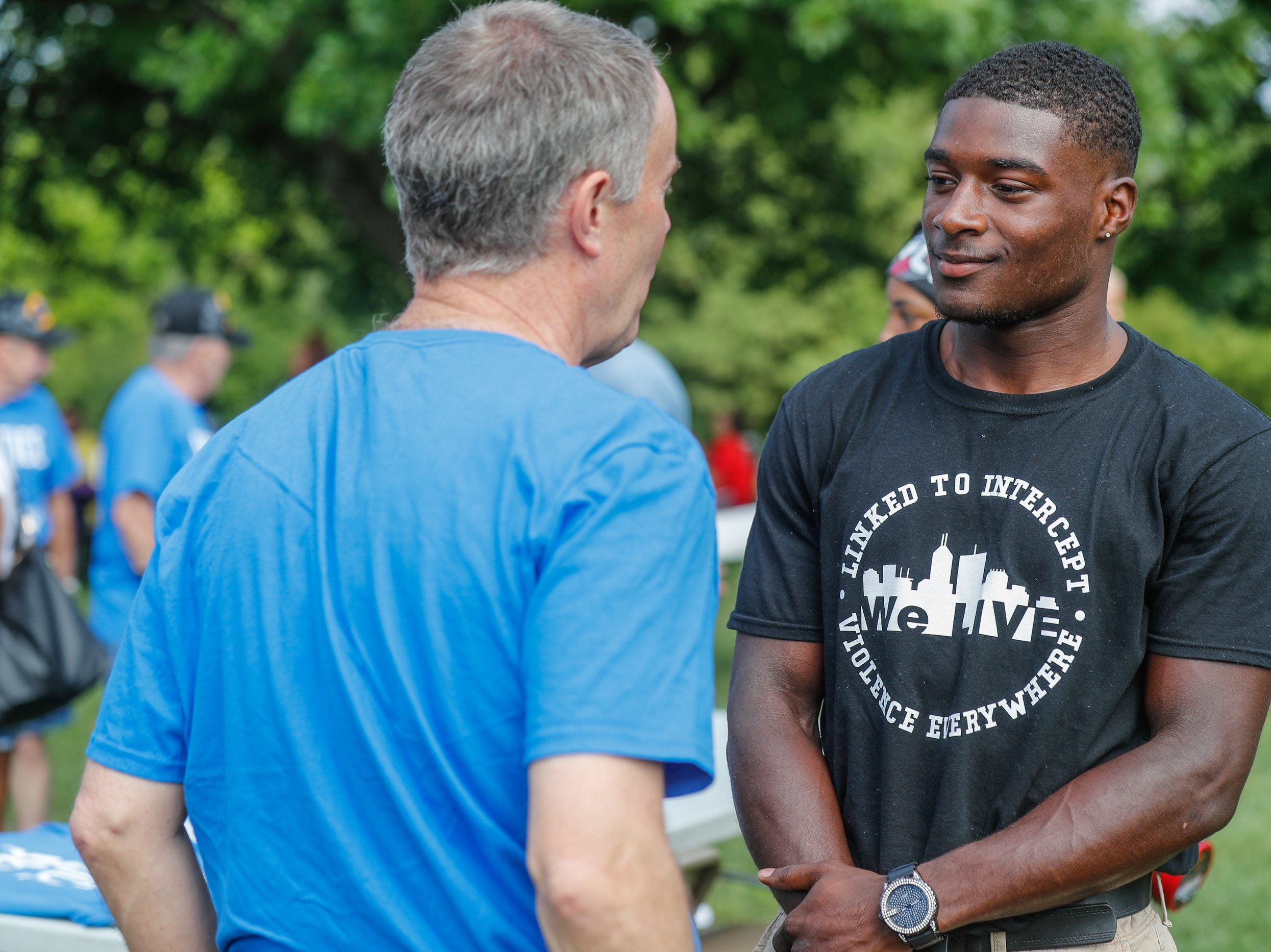 'We Live' President, Isaiah Warren, right, speaks with Indianapolis Mayor Joe Hogsett during the second annual Peace Walk and Community Day to end youth violence at Washington Park on Saturday, Aug. 11, 2018. 'We Live,' which stands for 'Linked To Intercept Violence' was started by students from Warren Central High School in Indianapolis.