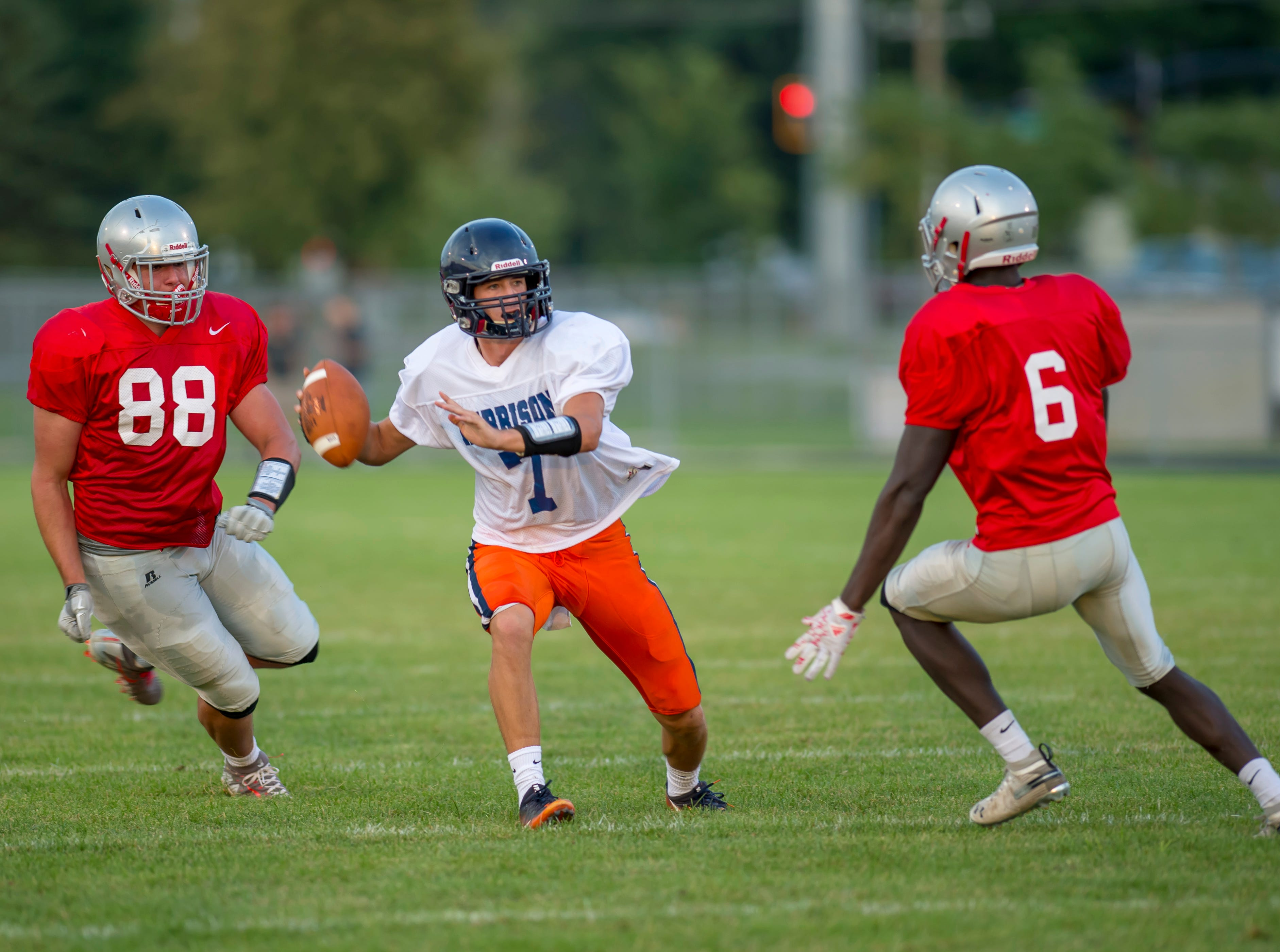 Andrew Jensen finds himself between George Karlaftis and Nelson Mbongo late in the football scrimmage between the Harrison Raiders and the West Lafayette Red Devils from Gordon Straley Field