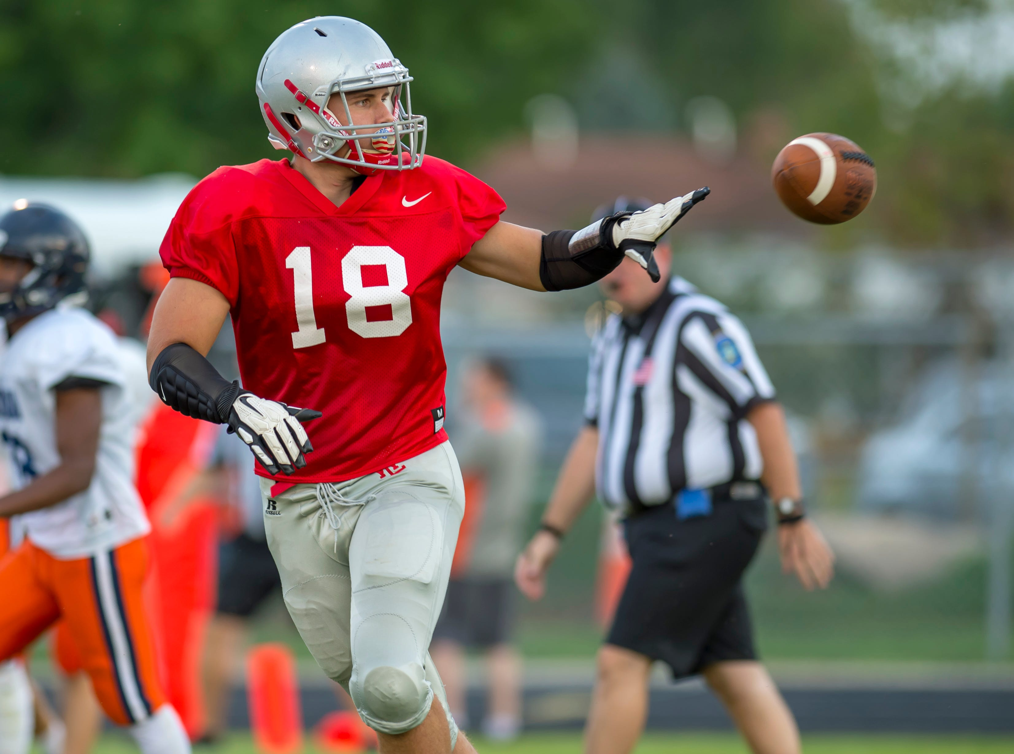 Sage Hood flips the ball to the referee after a West Side score in the football scrimmage between the Harrison Raiders and the West Lafayette Red Devils from Gordon Straley Field