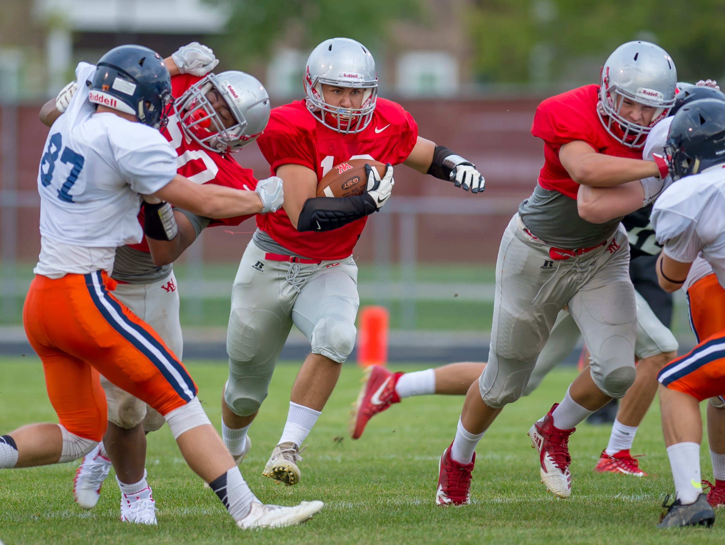 Sage Hood blasts through the line at the football scrimmage between the Harrison Raiders and the West Lafayette Red Devils from Gordon Straley Field