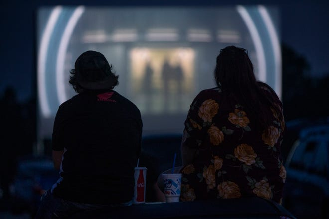 Travis Vaughn, left, and Kelsey Davenport, right, are  silhouetted by the movie, The Meg, on screen at the Sauerbeck Family Drive-in Theater. Aug.10, 2018.