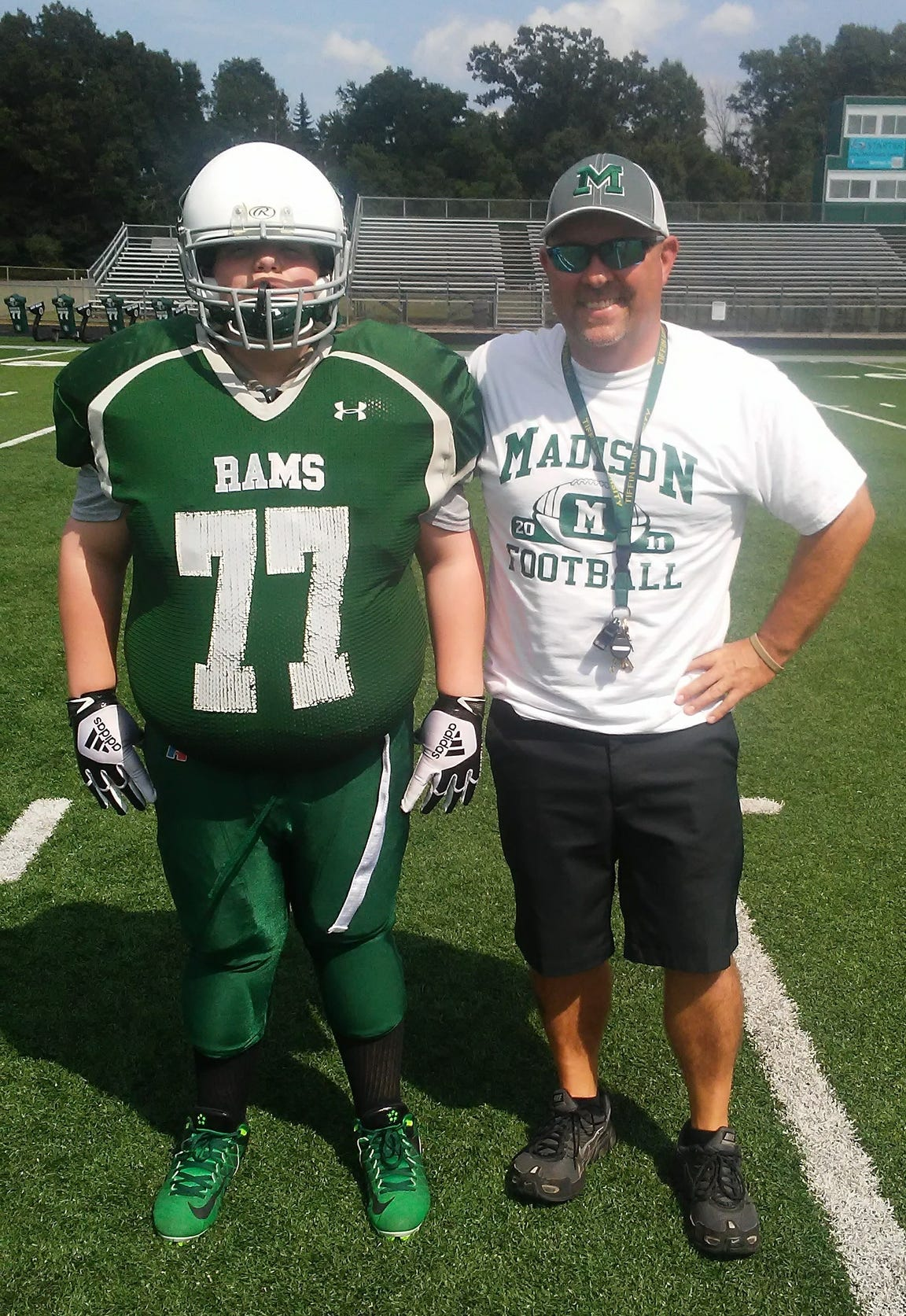 Elijah Bland (77) and his coach Tim Deel pose for a photo before picture day at Madison High School.